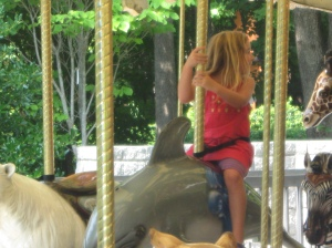 Riding a dolphin on the carousel
